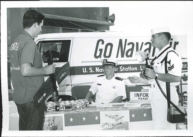 A model airplane enthusiast talks to a Navy recruiter and photographer at an Go Navy information booth.