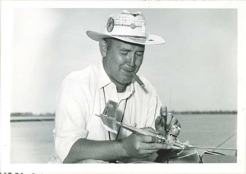 A man in a white hat is intently fixing a CL model airplane.