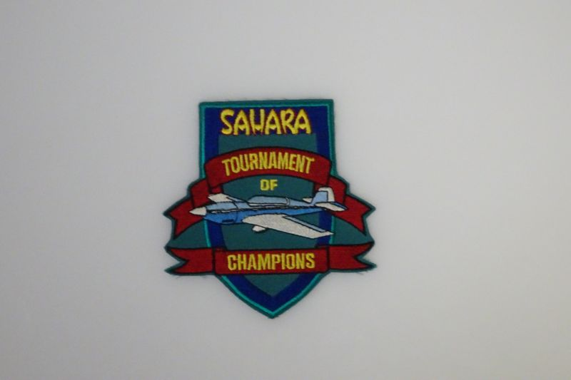 A shield-shaped patch in blue and teal showing a model airplane at center. Yellow writing advertises the Sahara Tournament of Champions. Possibly 1997.