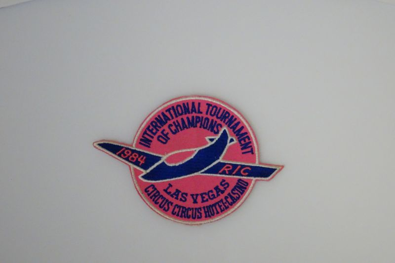 Bright pink patch with blue and white detailing of the circled plane logo of the 1984 Tournament of Champions.