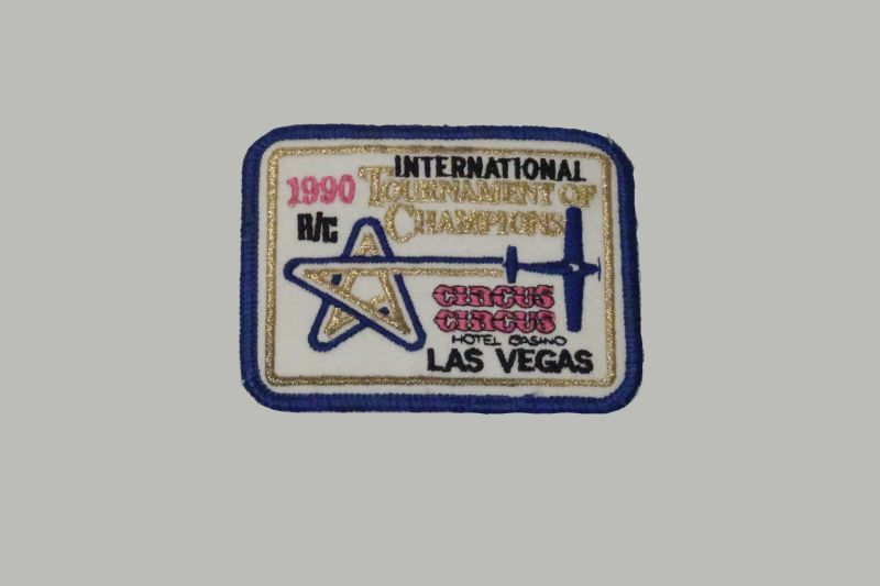 Rectanuglar patch with dark blue trim and a white background. The design is busy with a partial star and airplane in gold, blue and pink. - 1990