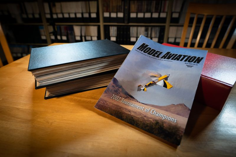 A magazine cover showing a large model flying low against a desert background. Bound magazines and library scene behind magazine.