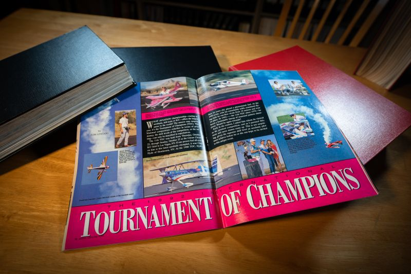 """A magazine opened to the center fold, showing lots of airplanes in flight and a giant pink blocked title at the bottom reading """"Tournament of Champions"""" - 1992."""